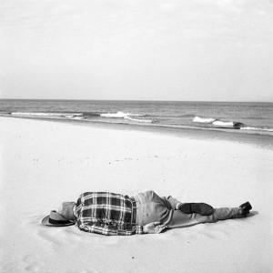 Hombre duerme en una playa de Flirda. Vivian Maier.