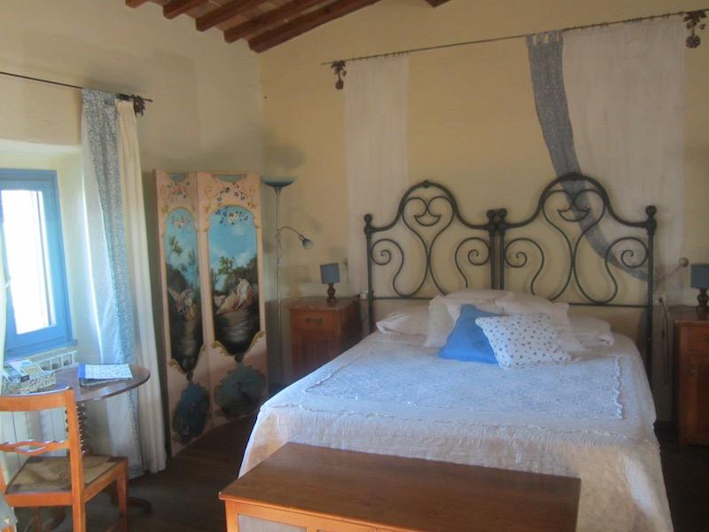 Habitación de un encantador B&B, decorada con trompe l'oil, y con techos con vigas de madera y terracota. Típico estilo toscano. ©María Calvo.