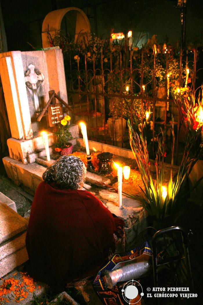 Señora rezando a sus muertos en el cementerio de Mixquic