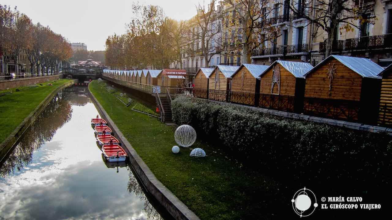 Chalets del mercado de Navidad vistos desde el puente. Se puede navegar en las barquitas por el río Têt