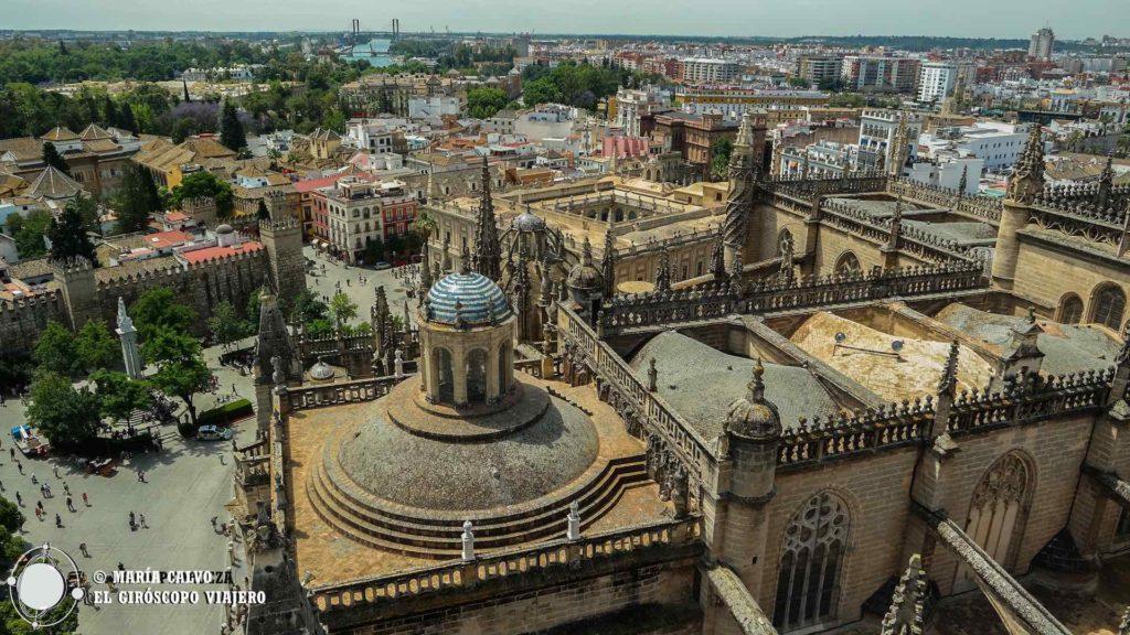 La belleza de Sevilla desde lo alto de la Giralda: la catedral en primer plano, el Real Alcázar a la izquierda, el Guadalquivir al fondo