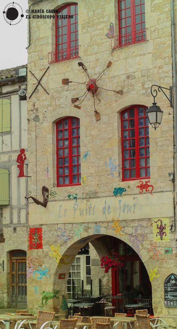 Un café lleno de color bajo los soportales de la plaza principal de Lauzerte