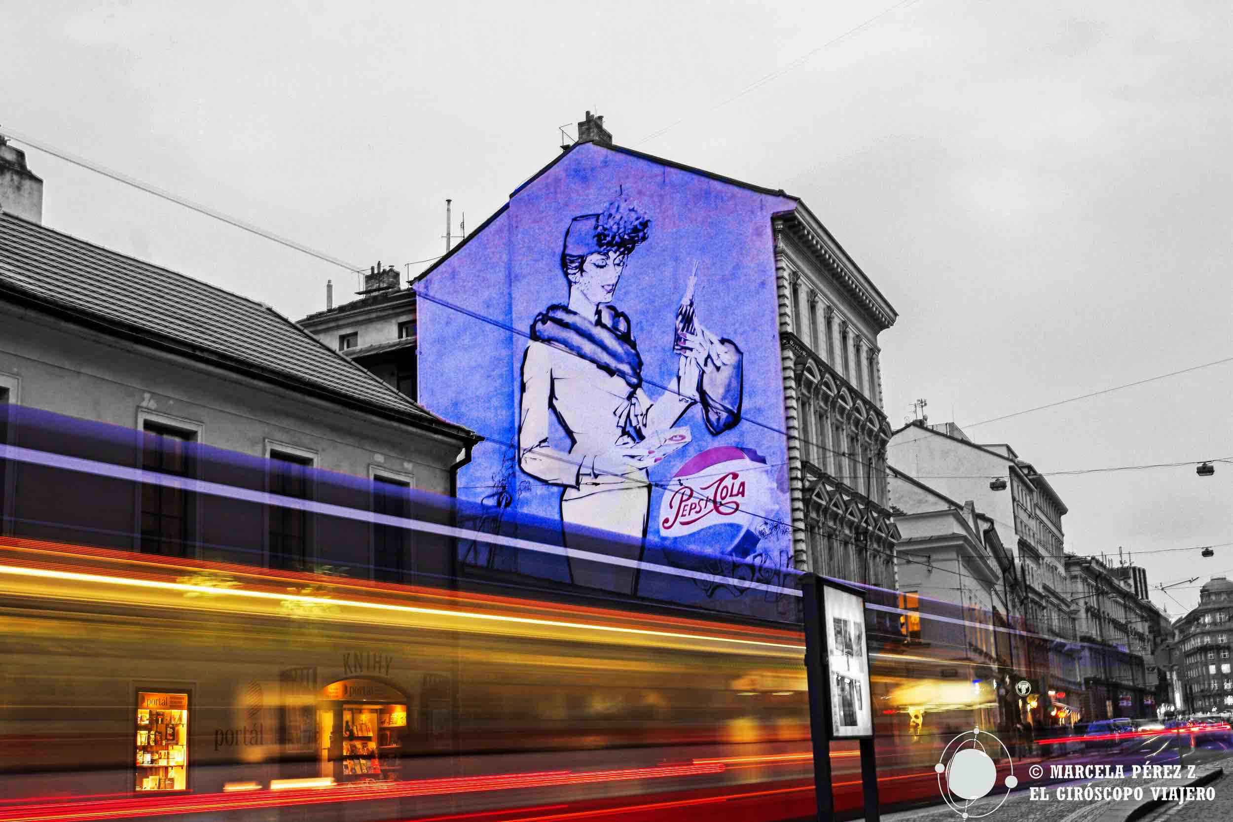 Tranvía de Praga con un graffiti en un edificio de Praga